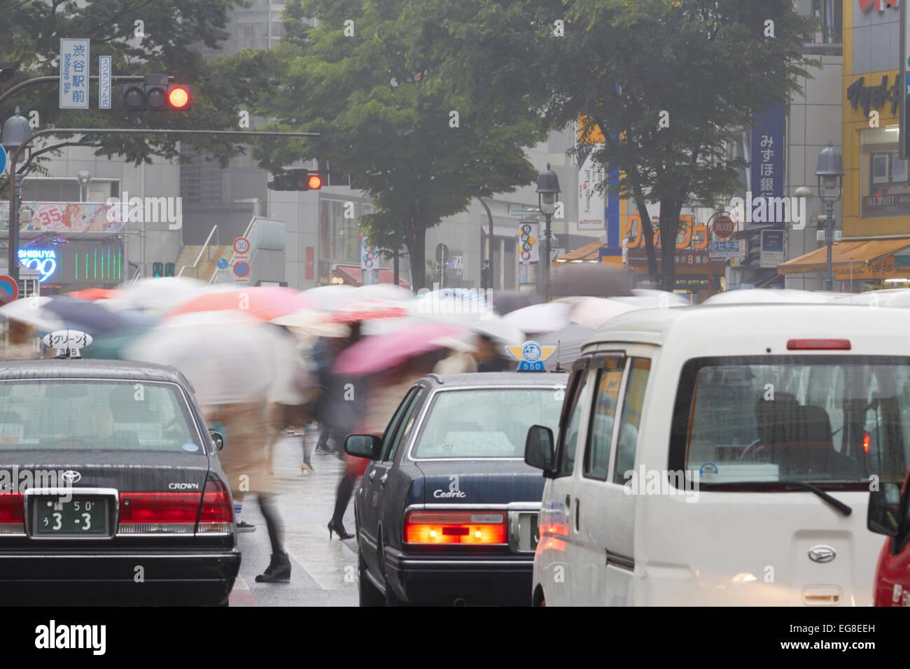 Pendler mit Sonnenschirmen beim Überqueren der Straße an einem regnerischen Tag, Shibuya, Tokyo, Japan Stockbild