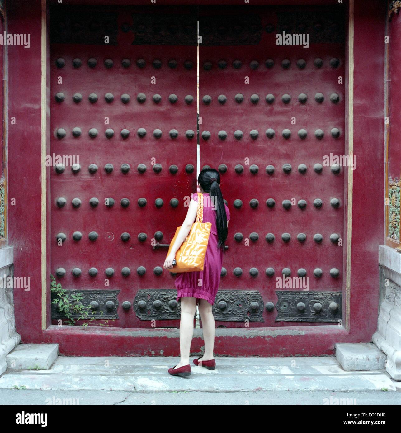 Frau spähen durch Tor, Verbotene Stadt, Peking, China Stockbild