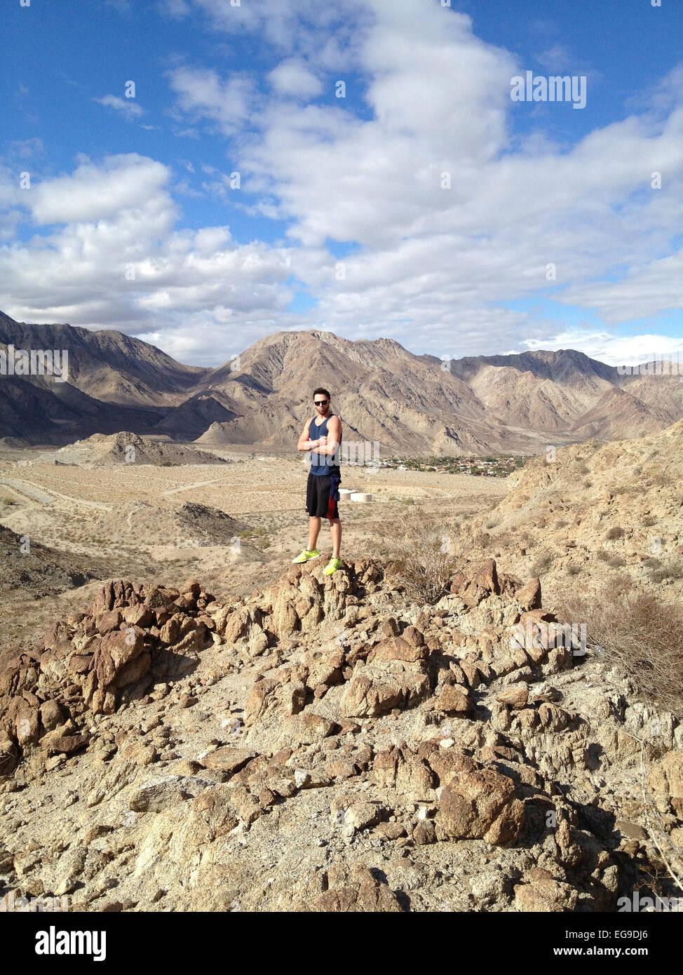 Mann auf Berggipfel mit Blick auf Tal Stockbild