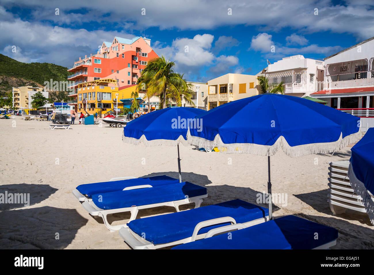Bunte Sonnenschirme und Liege liegen am Strand von Philipsburg, St. Maarten, Karibik-Insel. Stockbild