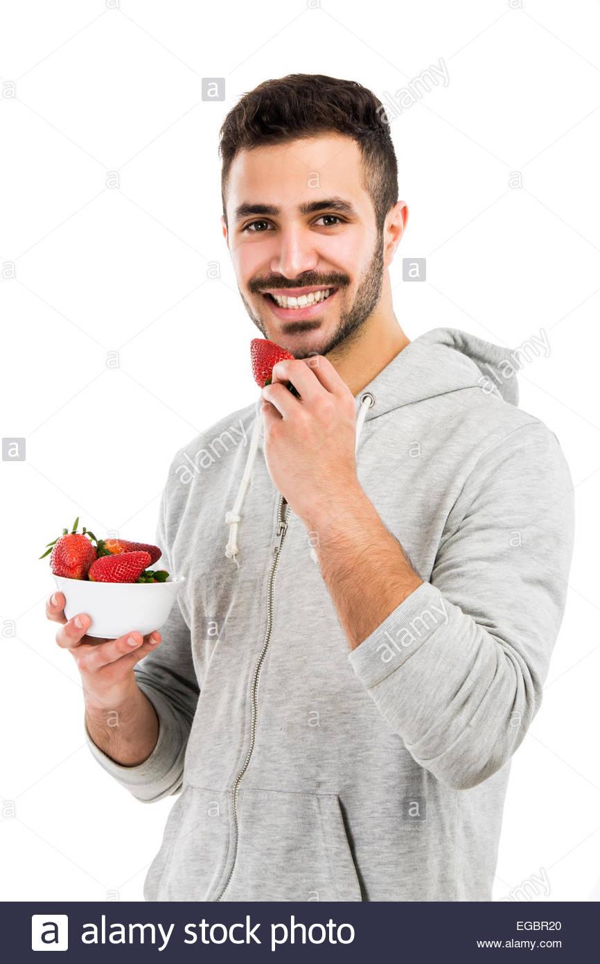 gl cklich j ngling essen eine erdbeere isoliert auf wei em hintergrund stockfoto bild. Black Bedroom Furniture Sets. Home Design Ideas