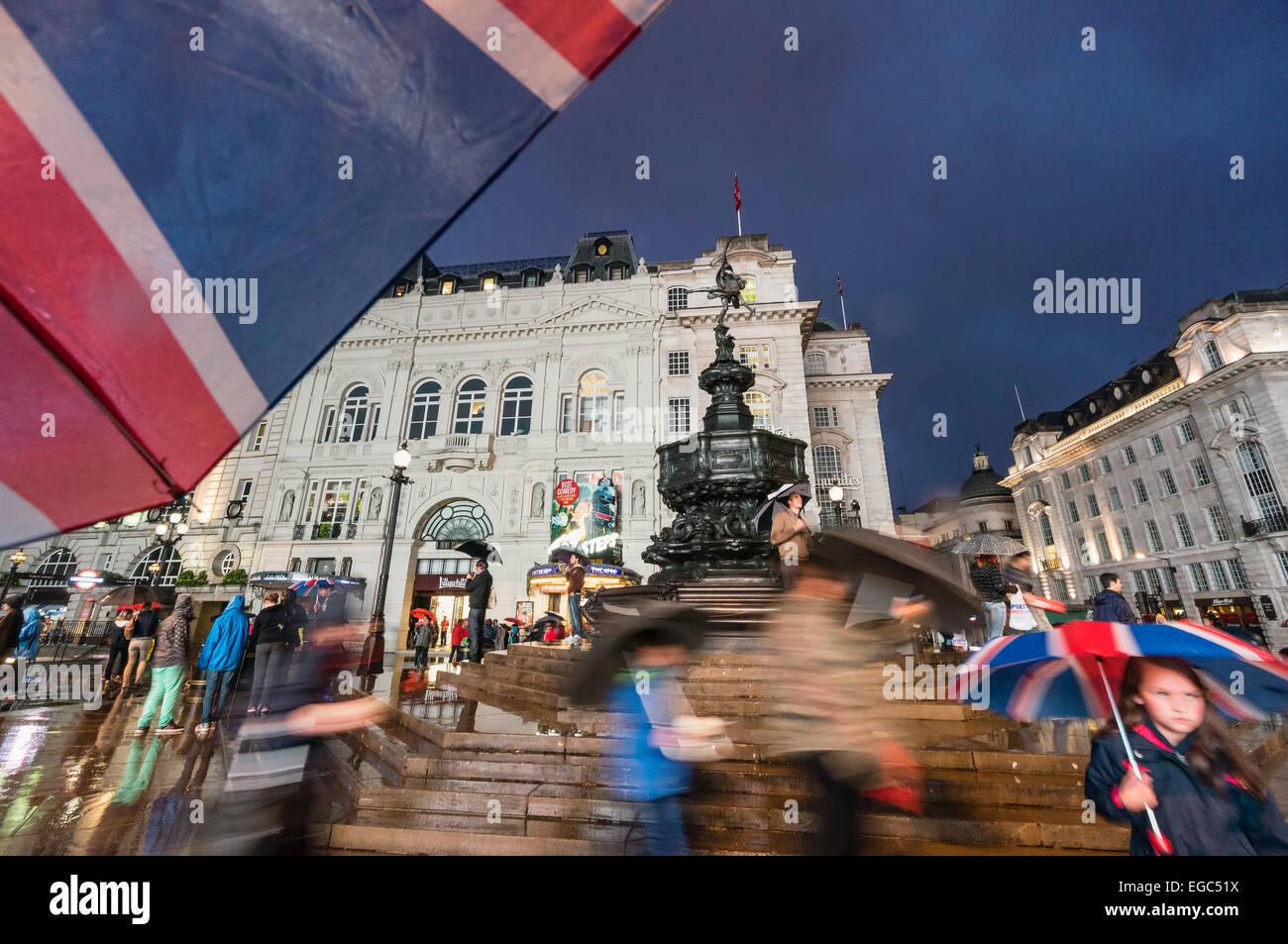 Menschen mit Sonnenschirmen am Piccadilly Circus in der Nacht, London, UK Stockbild