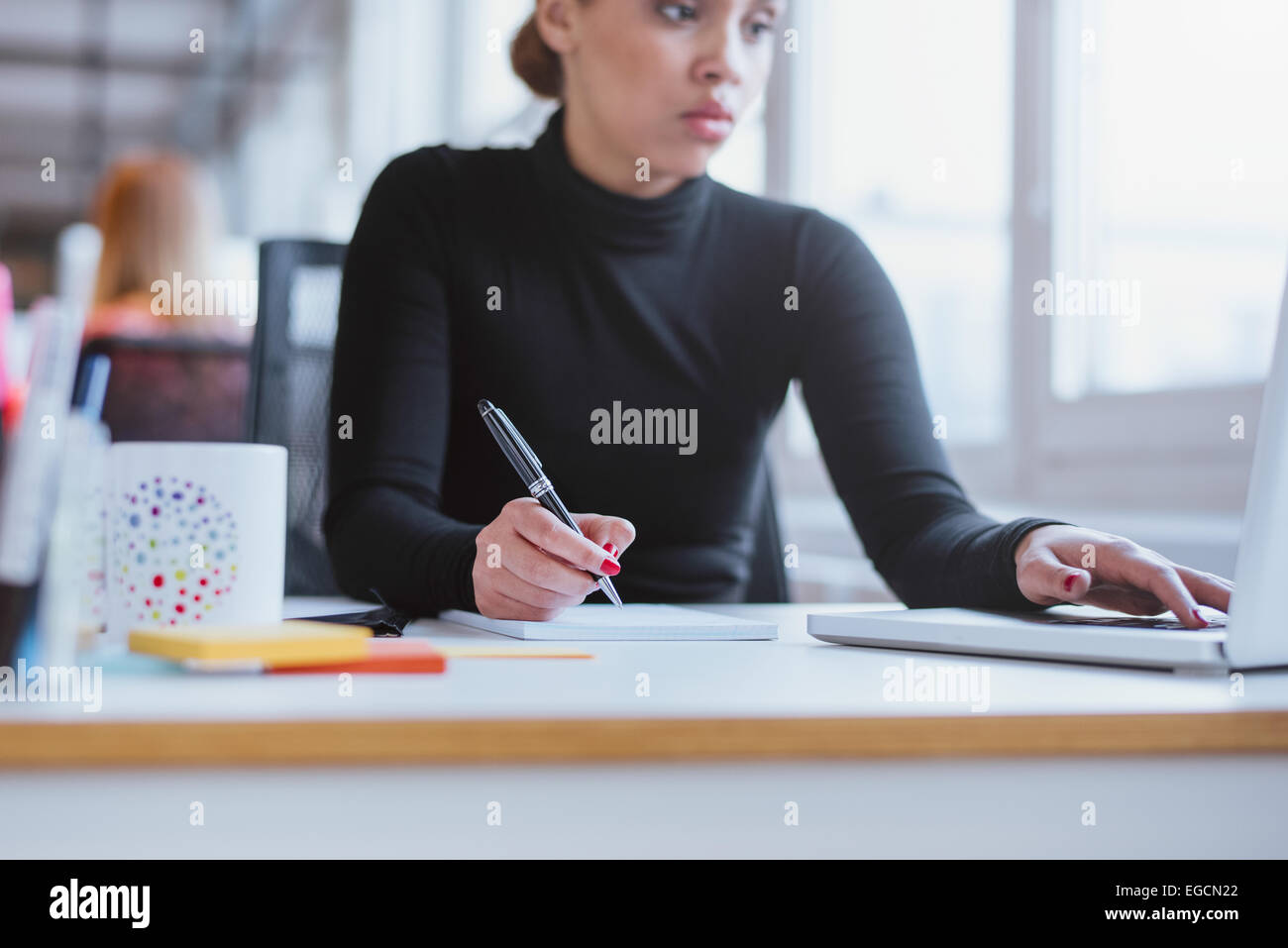 Junge Frau Notizen von Laptop. Weibliche Führungskraft ihrem Schreibtisch mit Laptop und Schreiben von Notizen Stockbild
