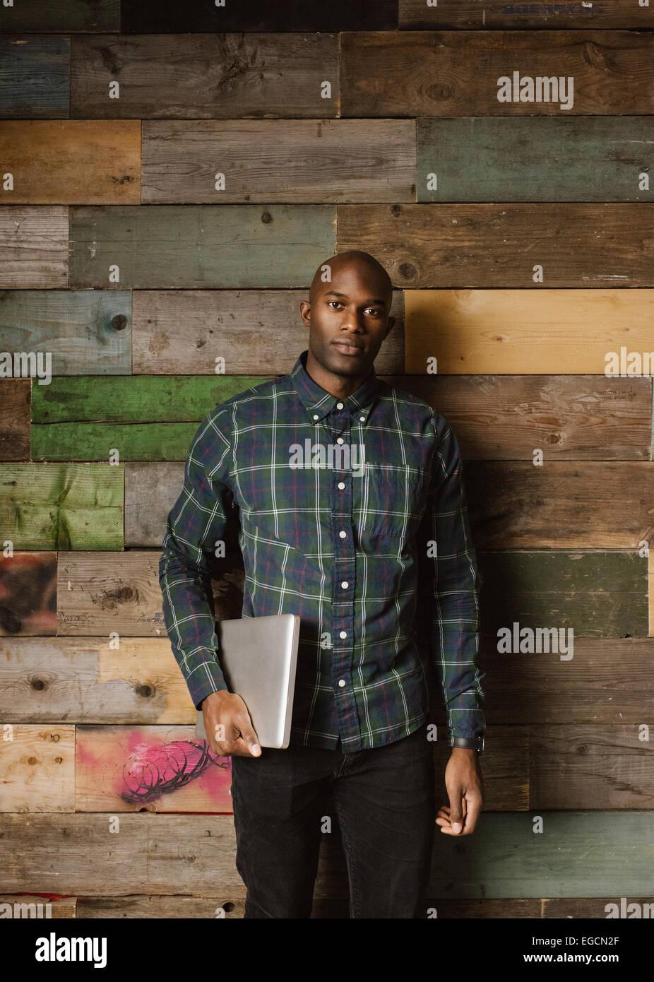 Porträt eines schönen jungen Geschäftsmann lehnt sich an eine Holzwand mit einem laptop Stockbild