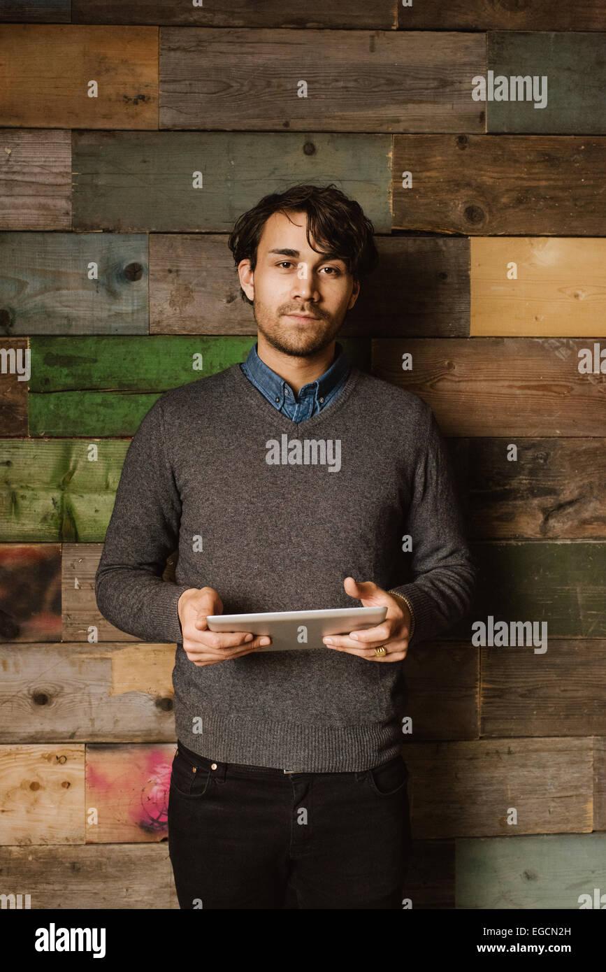 Porträt von zuversichtlich junger Mann hält eine digitale-Tablette Blick in die Kamera. Führungskraft Stockbild