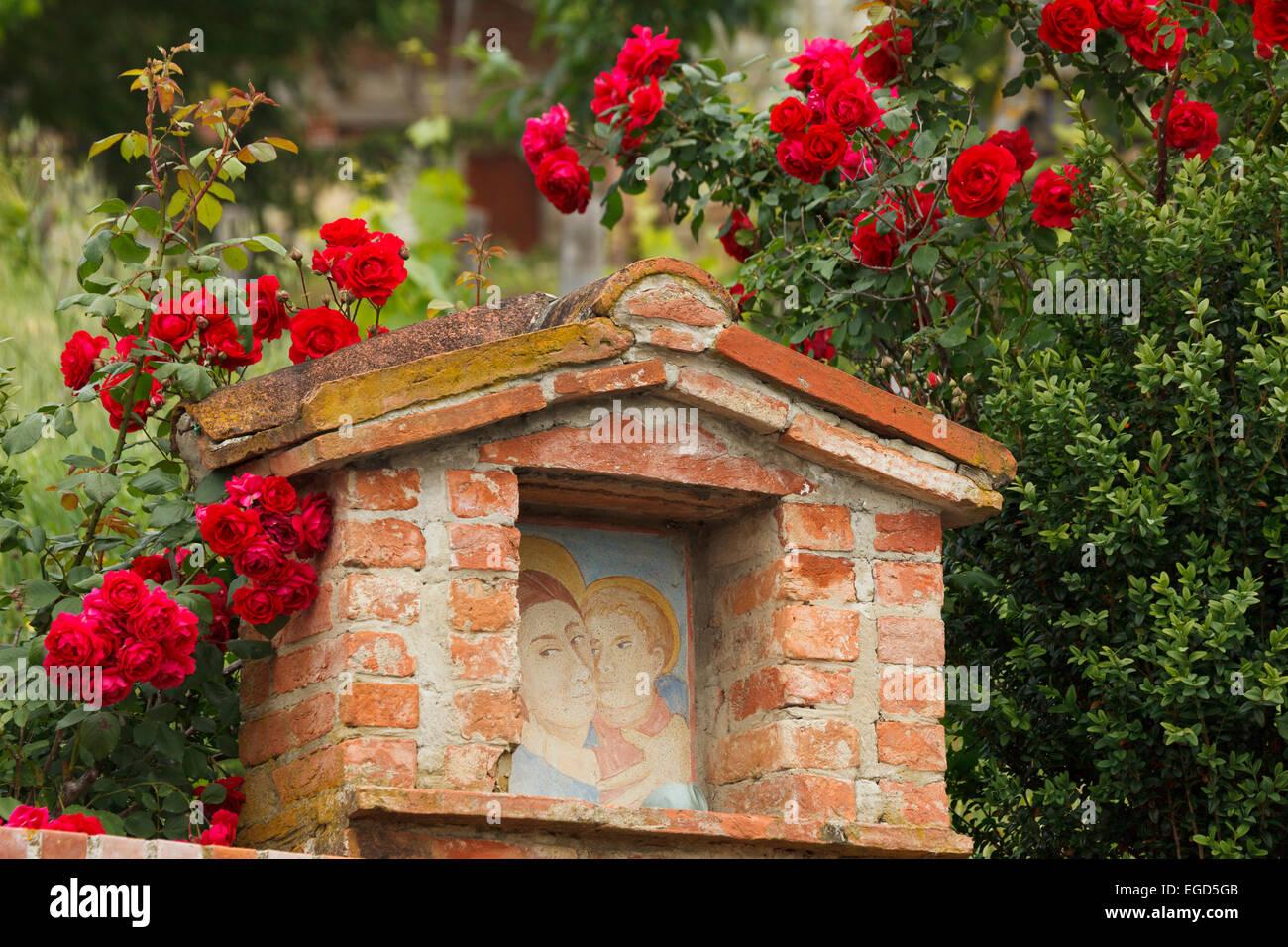 Christlichen Bildstock, umgeben von Rosen in der Nähe von Taverne D´Arbia, Val d ' Orcia, Orcia-Tals, Stockbild