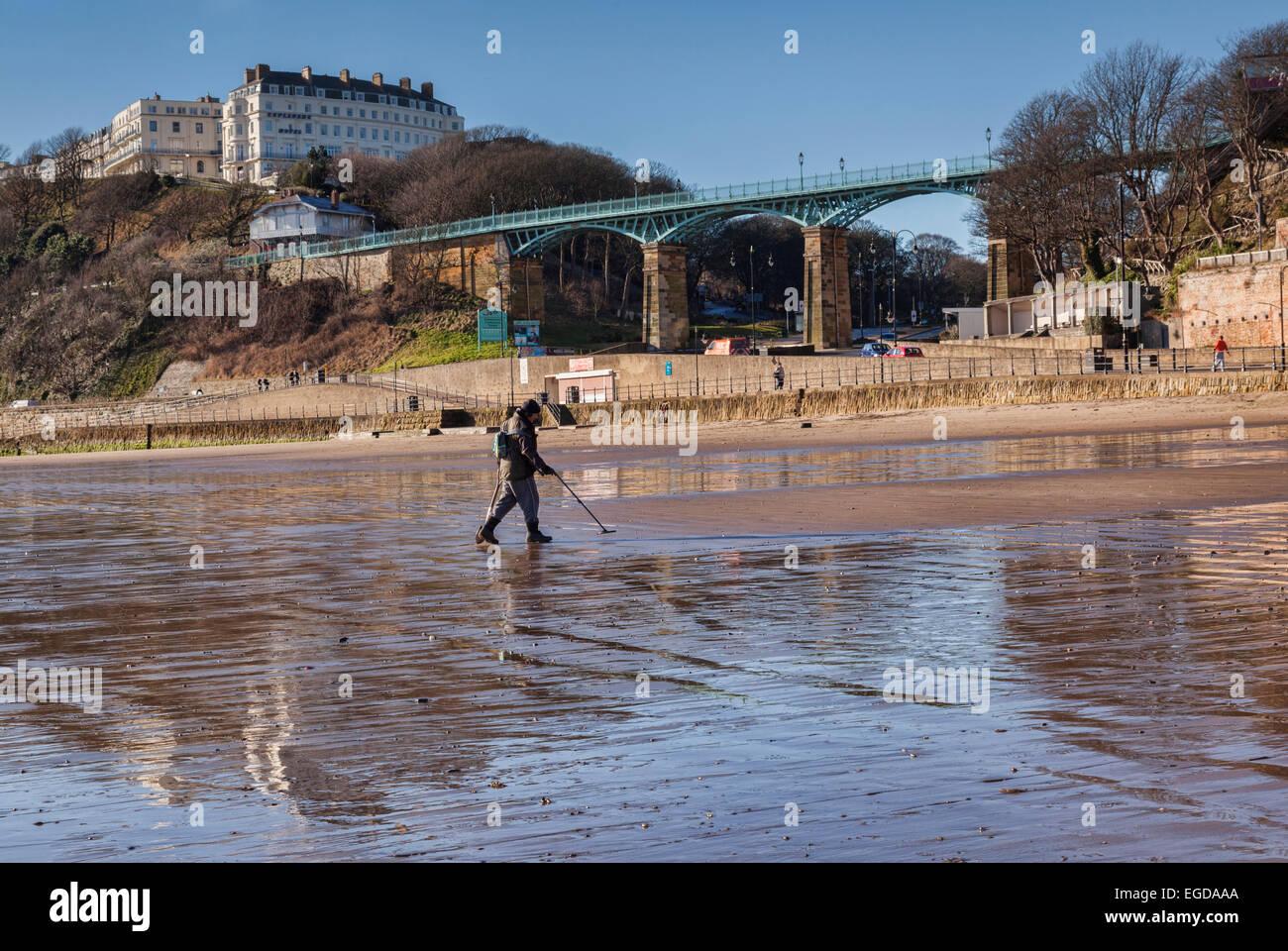 Mann, Metalldetektoren am Scarborough Strand. Im Hintergrund sind die Spa-Brücke und das Hotel Esplanade. Stockbild