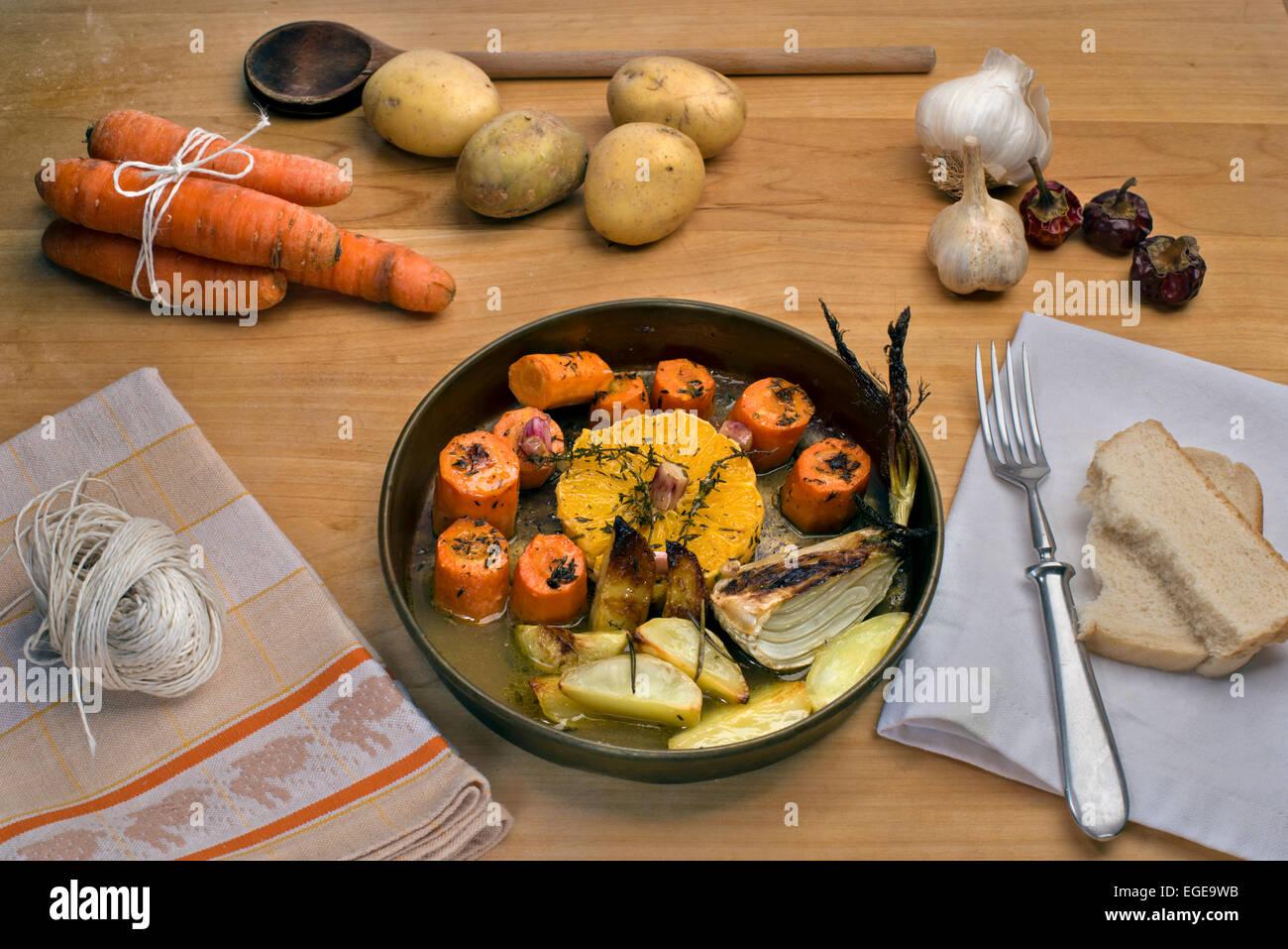 Karotten in Weißwein mit Orangen, Knoblauch, frischem Thymian und Butter gebraten serviert mit gebraten Rosmarinkartoffeln Stockbild