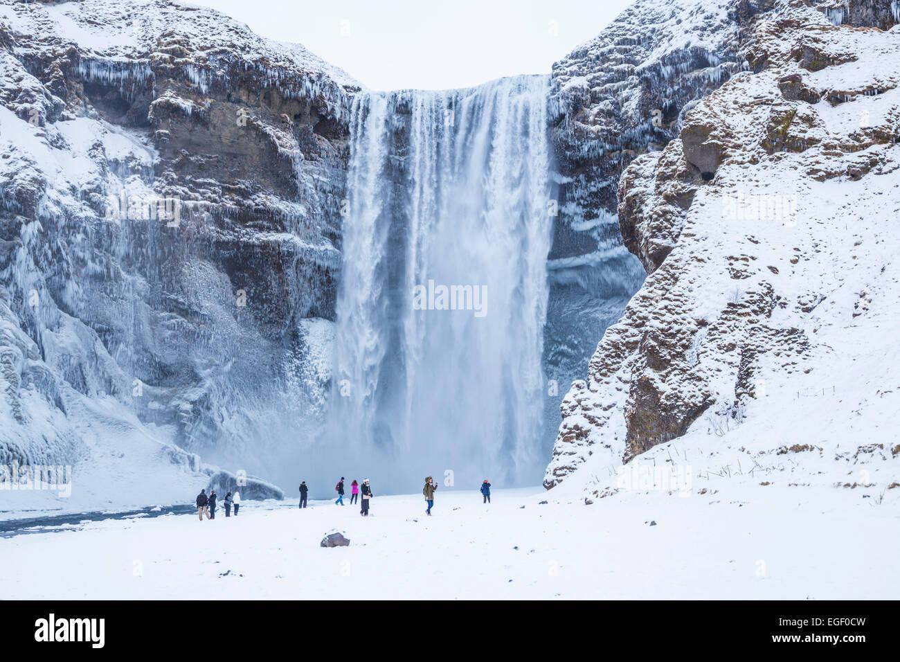 Touristen besuchen Skogafoss Wasserfall im Winter Skogar Süd-Island-Island-Europa Stockbild