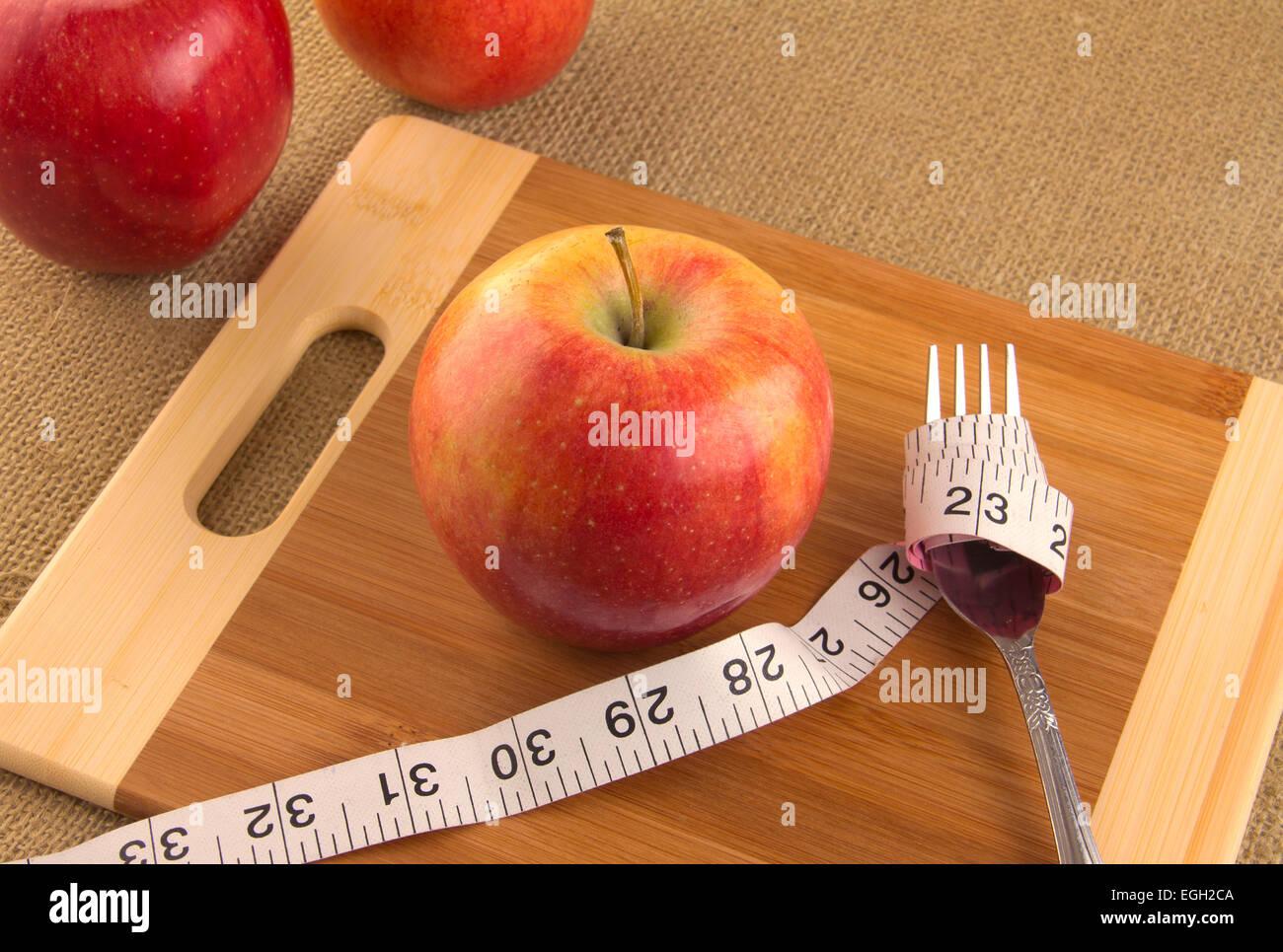 Gesunde Ernährung und Ernährung für Gewicht-Verlust-Konzept mit Apfel und Maßband Stockbild