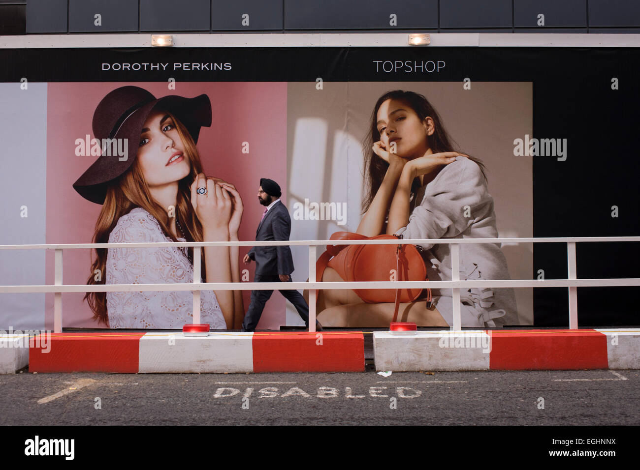 Sikh Mann geht vorbei an großen Bildern der westlichen Mode Model Mädchen. Stockbild