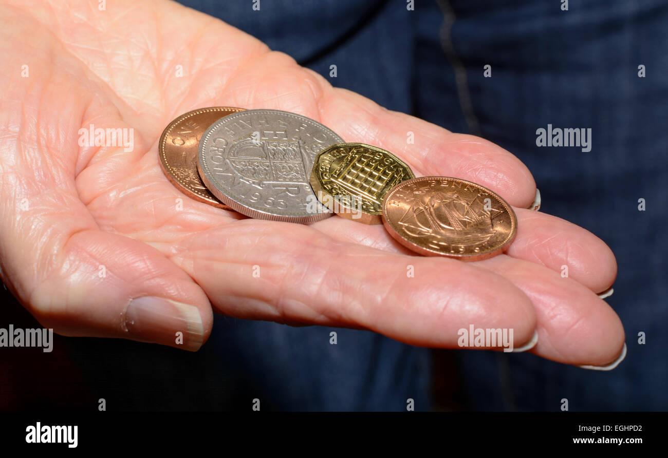 Mehrere alte Pre-decimal Münzen in die Hand einer Person. Stockbild