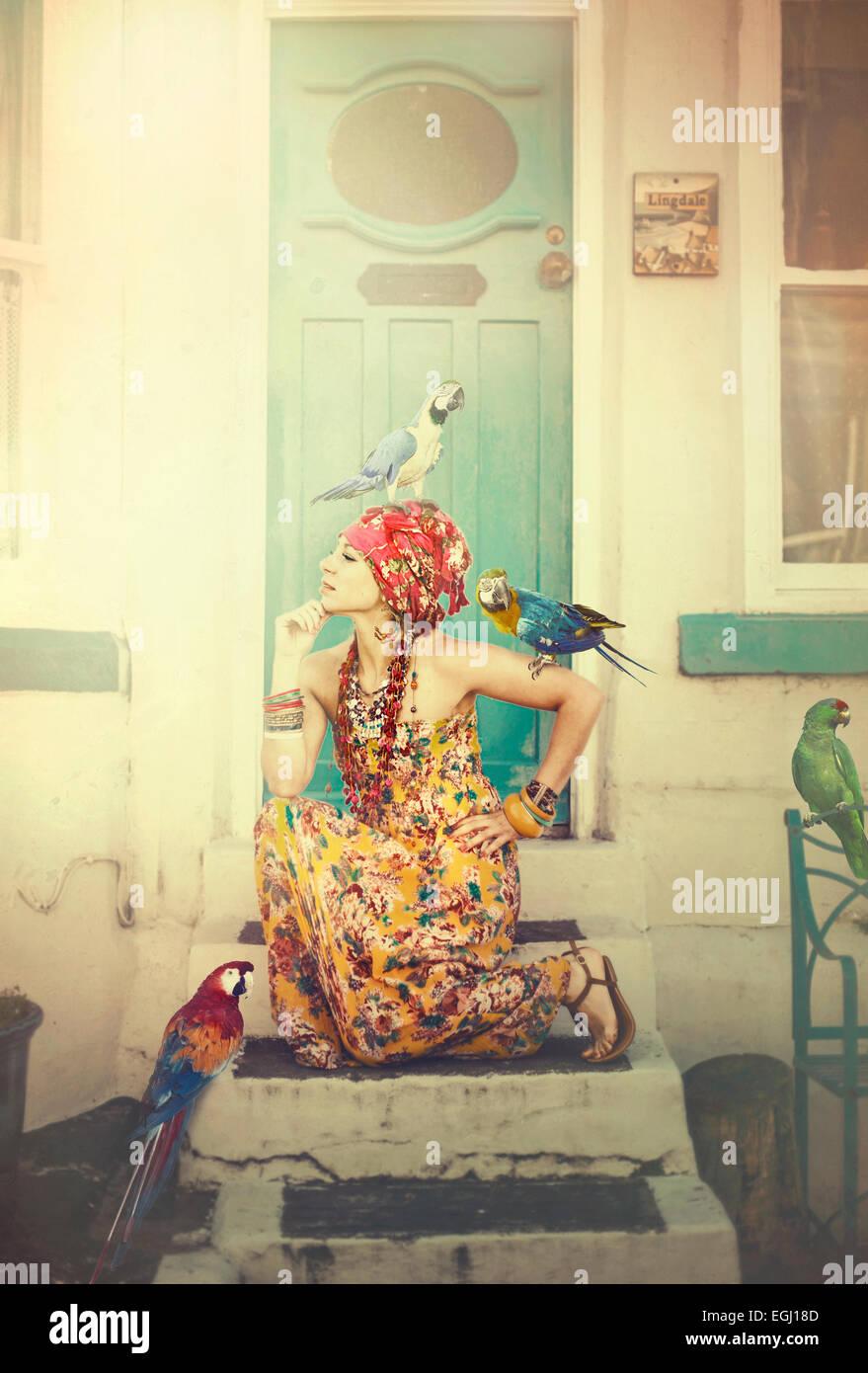 junge Frau posiert auf Treppen mit Papageien Stockbild