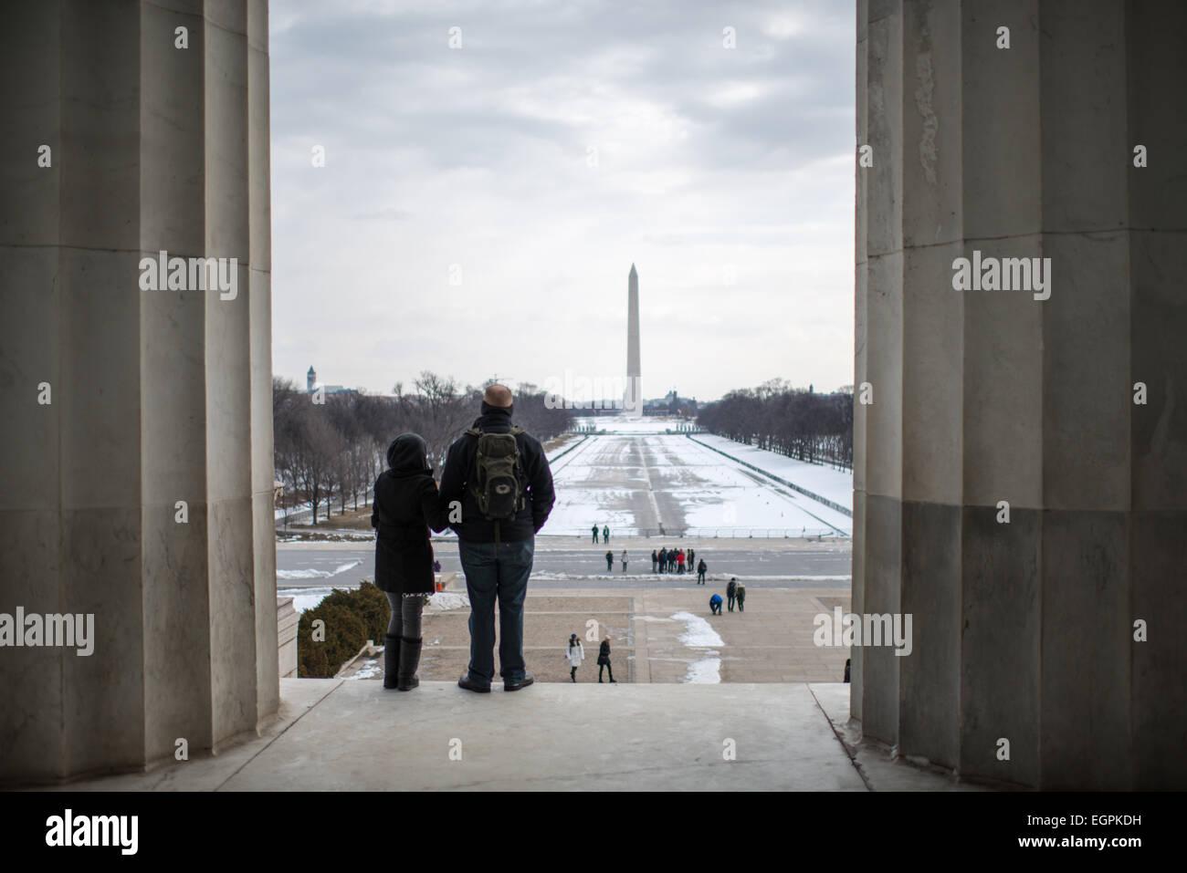 Touristen blicken von oben auf den Stufen des Lincoln Memorial auf dem Reflecting Pool (im Winter entleert) auf Stockbild