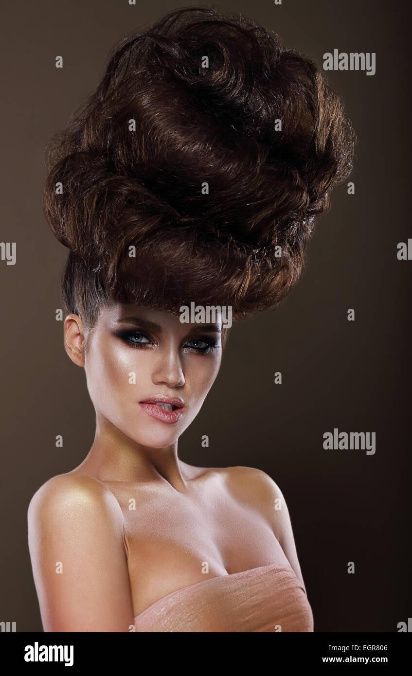 Hochsteckfrisur. Trendige Frau mit kreative Frisur Stockbild