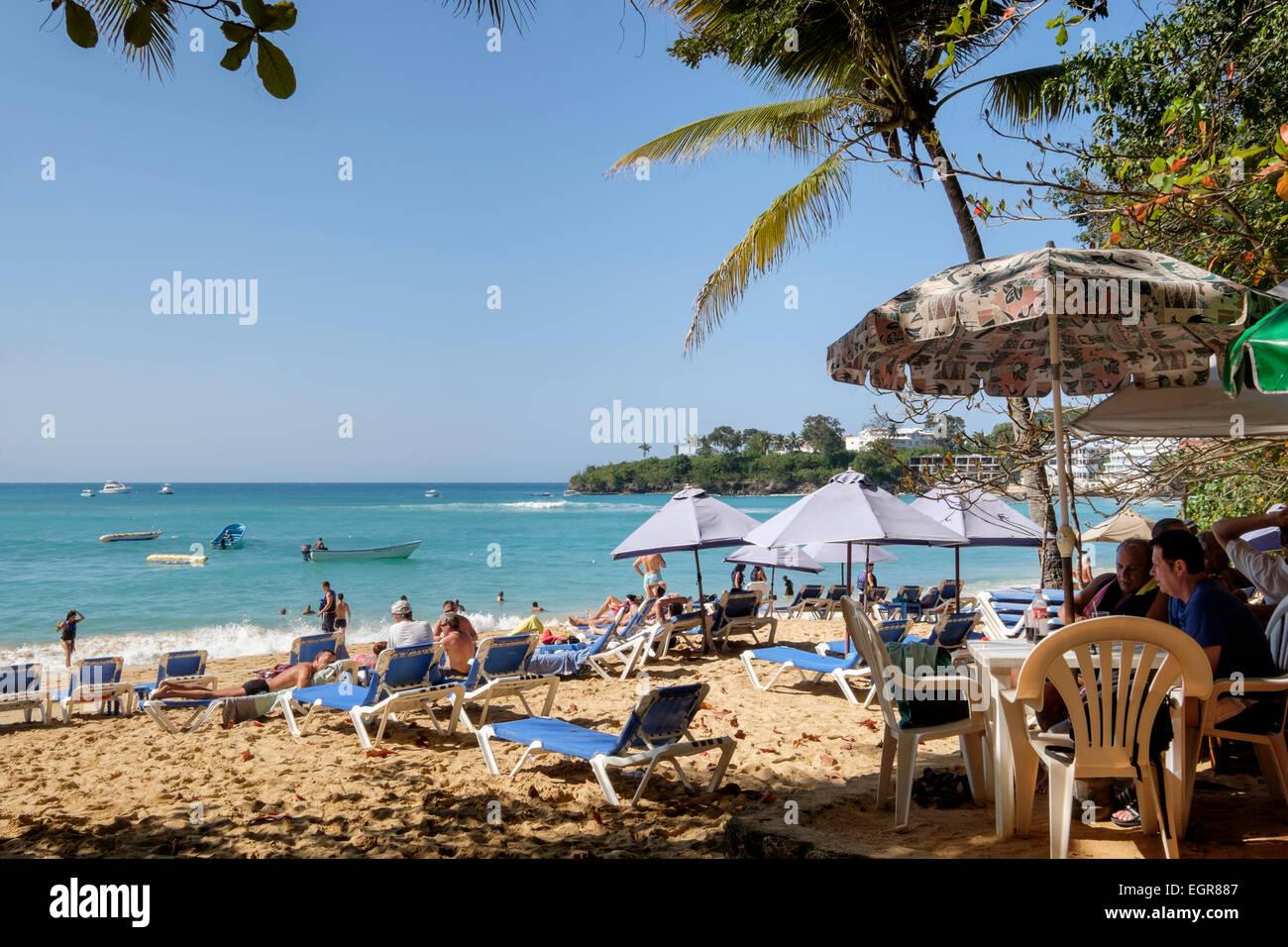 Strandbar und Touristen auf sandigen Strand mit Meer im Ferienort Sosua, Puerto Plata, Dominikanische Republik, Stockfoto