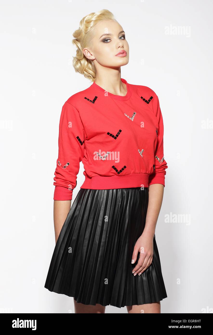 Trendige Blond in rote Bluse und schwarzem Rock Stockbild