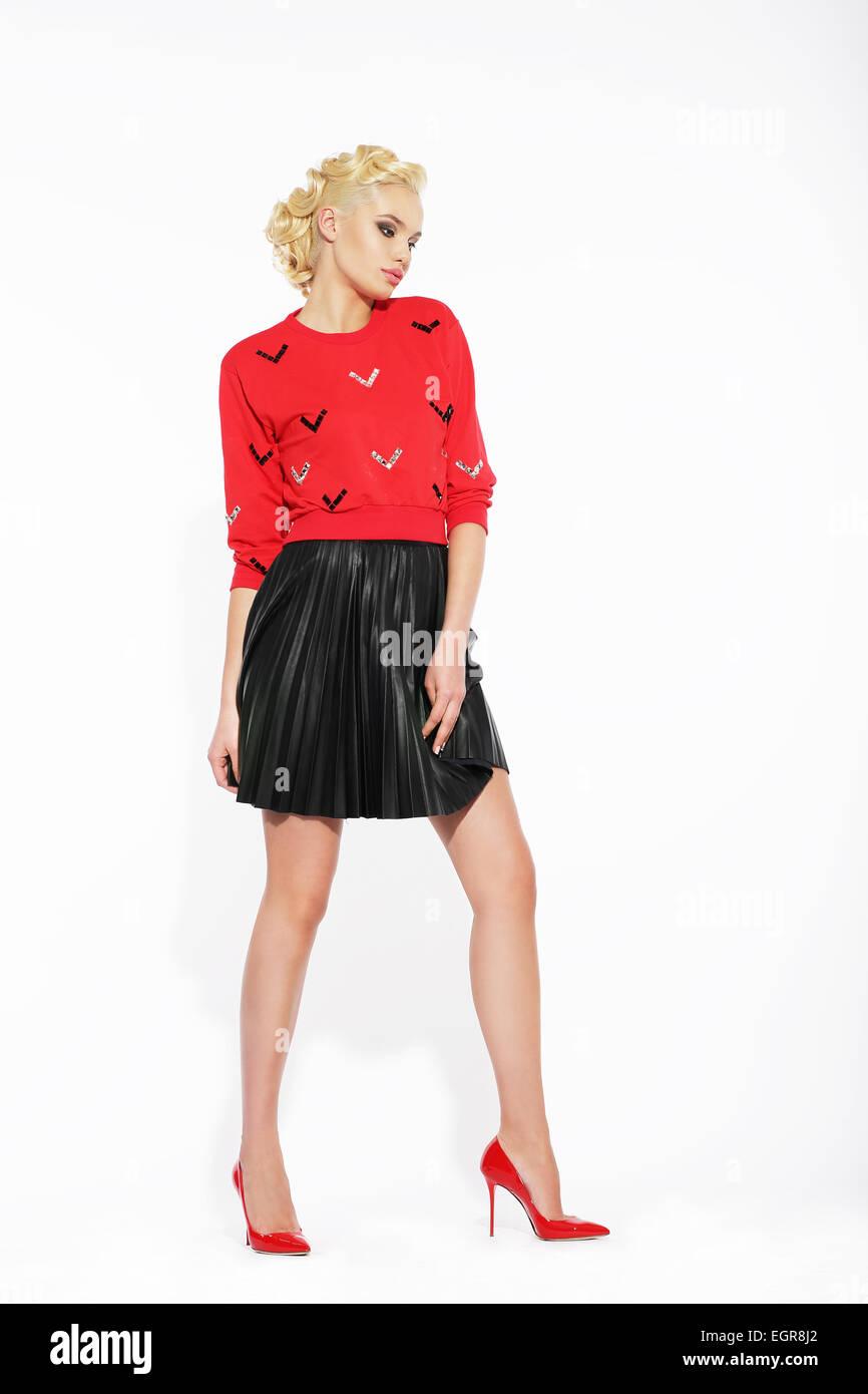 3c5cbae0d56c5b Elegante Blondine in schwarzen Rüschen Rock und rote Bluse Stockfoto ...