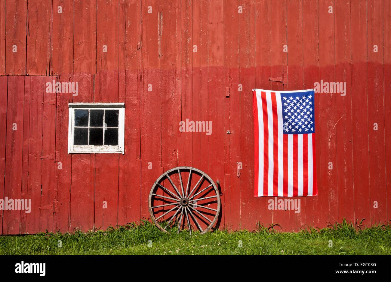 Historische rote Scheune, US-Flagge und ein antikes Wagenrad auf einem Bauernhof, Middlesex County, Monroe Twp., Stockbild