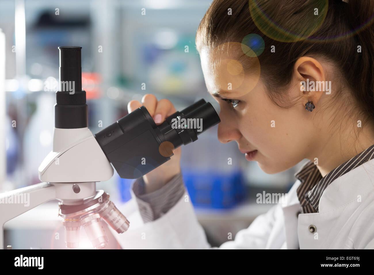 Wissenschaftler junge Frau unter Verwendung eines Mikroskops in einem wissenschaftlichen Labor Stockbild