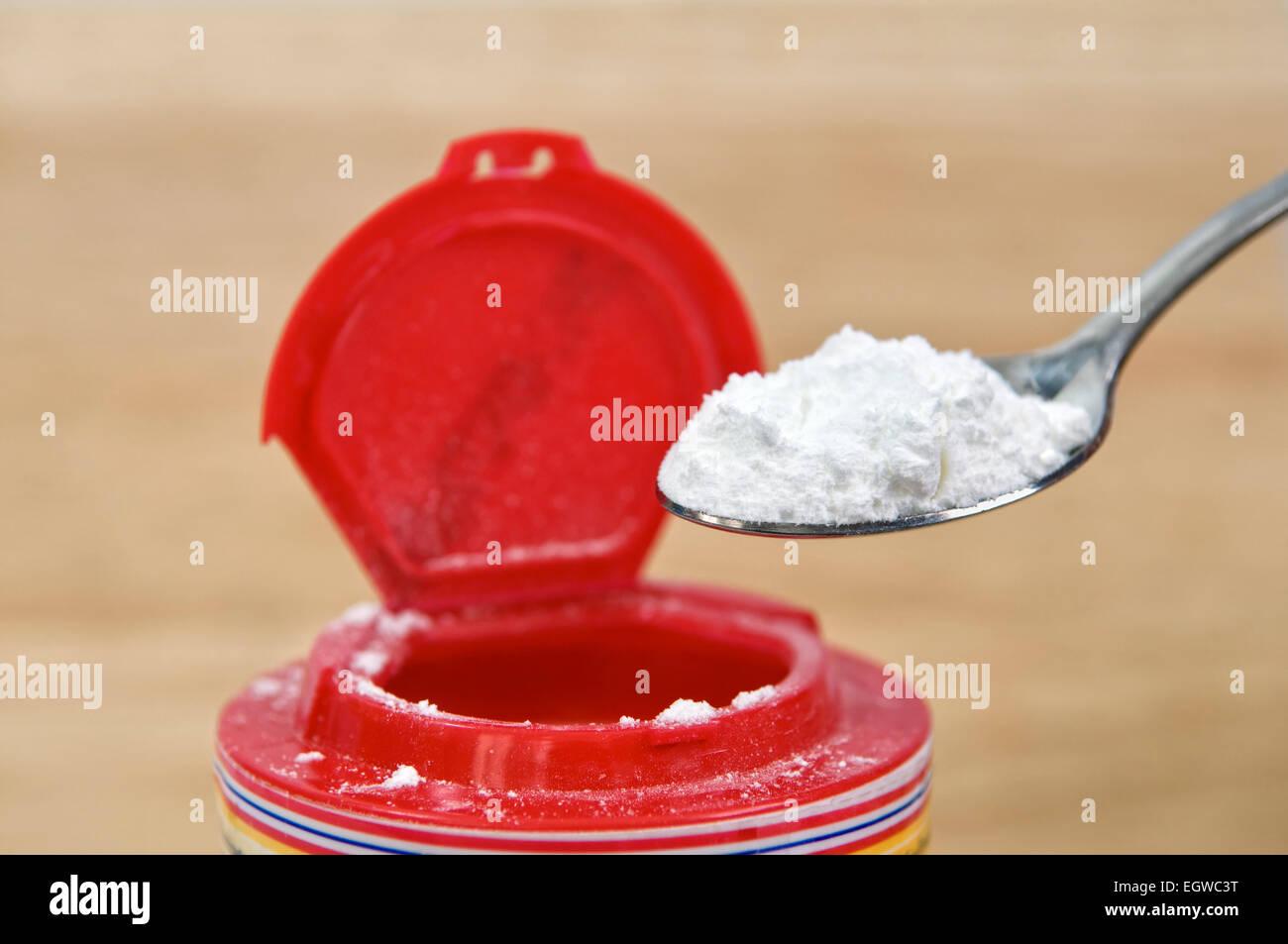 Einen Teelöffel Backpulver herausnehmen aus Behälter Stockbild
