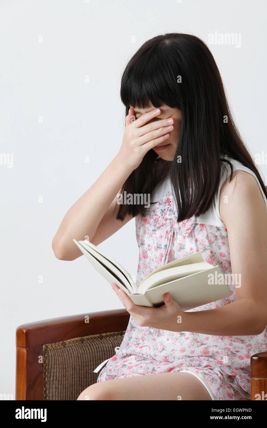 Chinesisches Mädchen lesen schreckliche Geschichte Stockbild