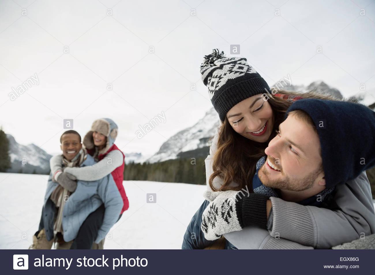 Paare in schneebedeckten Feld Huckepack Stockbild