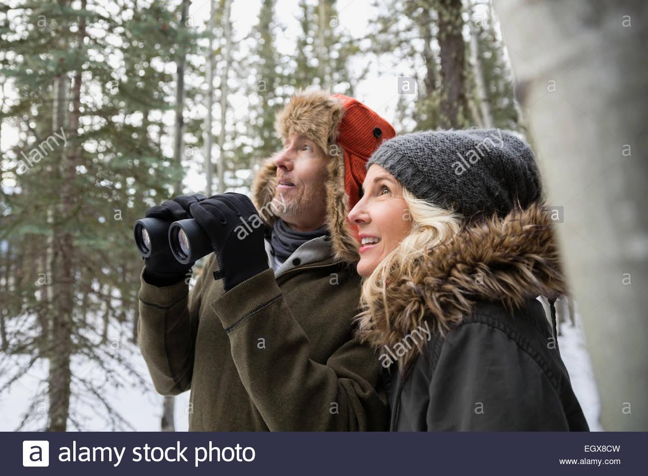 Paar mit fernglas vogelbeobachtung im verschneiten wald stockfoto