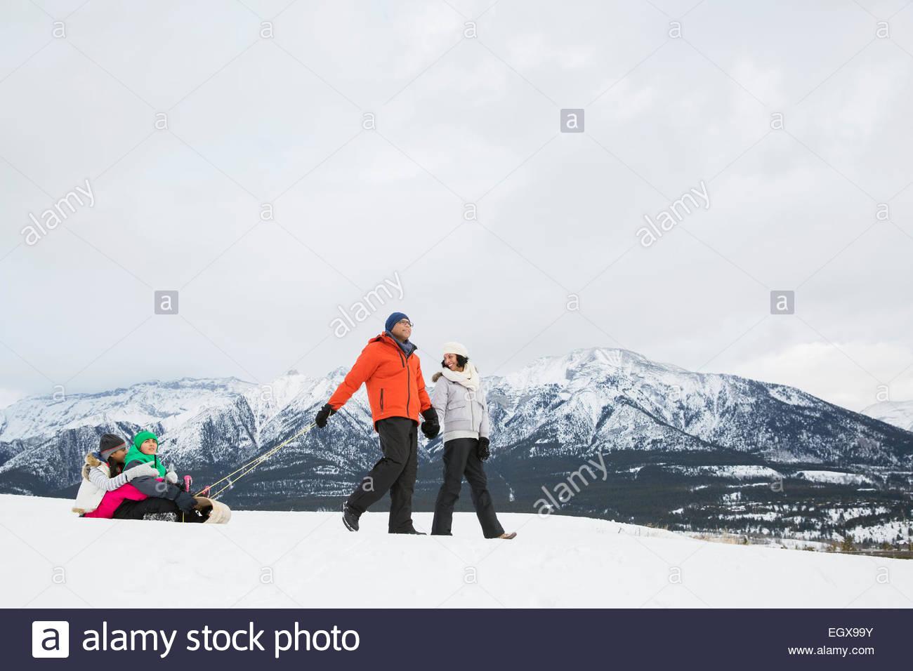 Eltern, die Kinder auf Schlitten in schneebedeckten Feld ziehen Stockbild
