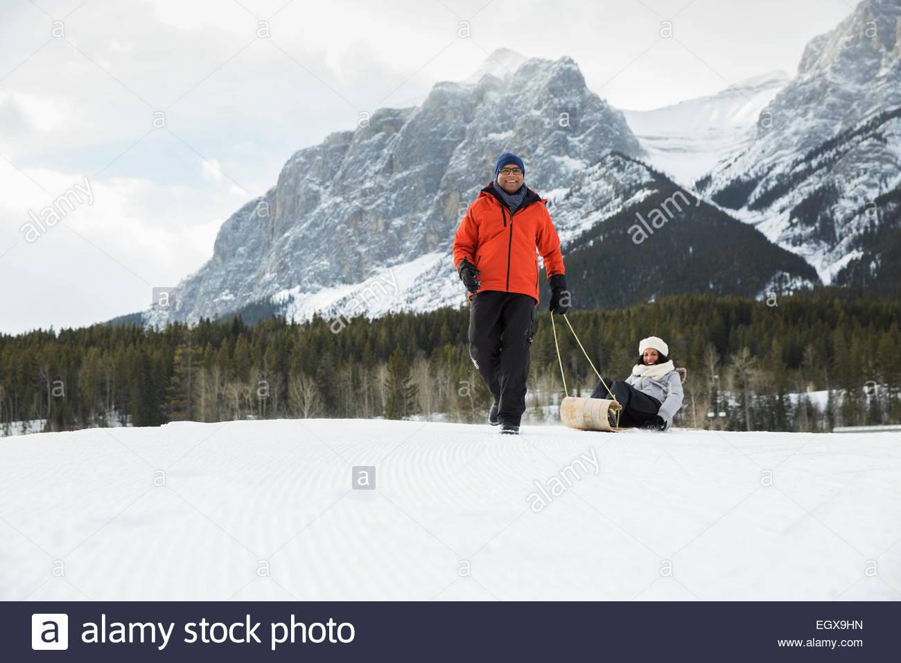 Mann Frau auf Schlitten in schneebedeckten Feld ziehen Stockbild