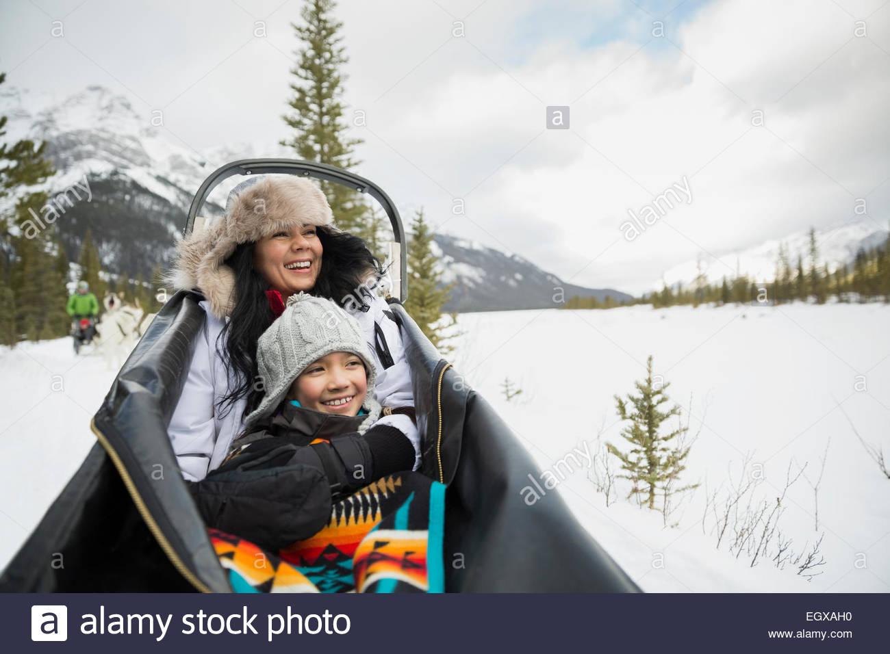 Lächelnde Mutter und Tochter im Hundeschlitten fahren Stockbild