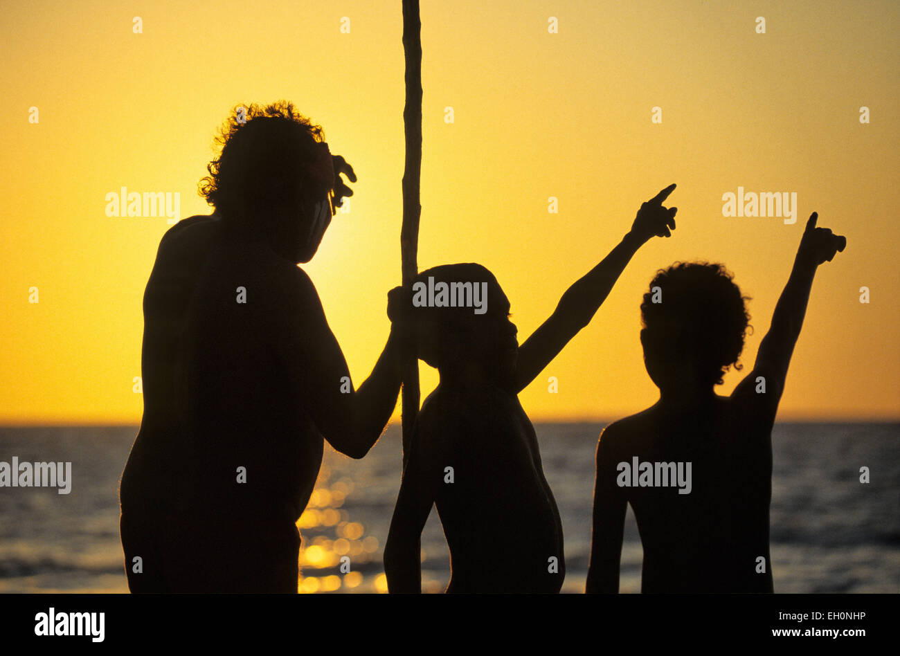 Aborigines mit einem Mast und Kindern zeigt auf den Himmel bei Sonnenuntergang, Darwin, Australien Stockfoto