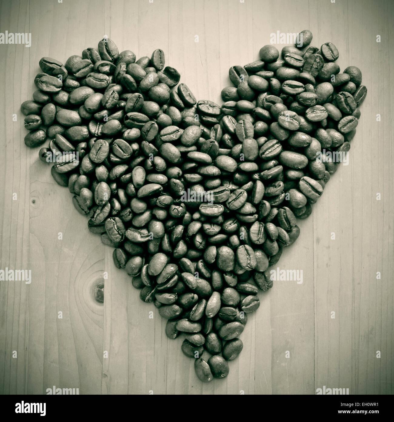 ein Haufen von gerösteten Kaffeebohnen bilden eine Herz auf einem Holztisch, in schwarz und weiß Stockbild