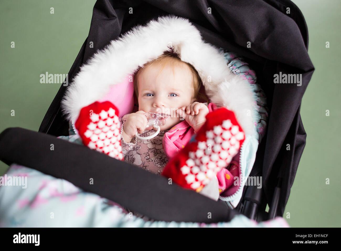 Porträt von niedlichen Baby Girl mit Schnuller in Kutsche vor grünem Hintergrund Stockbild