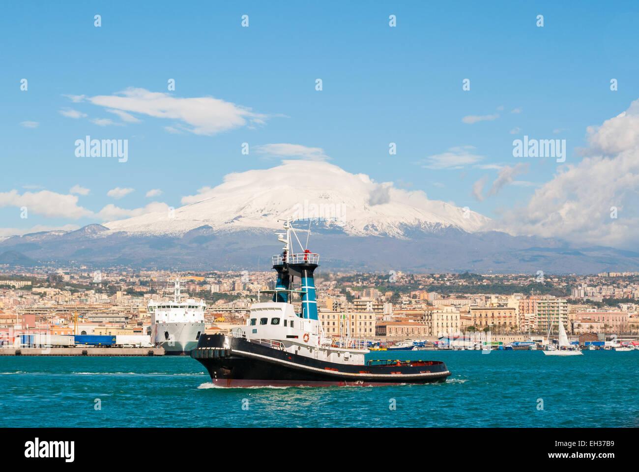 Ein Schlepper verlassen den Hafen von Catania. Vulkan Ätna im Hintergrund Stockbild