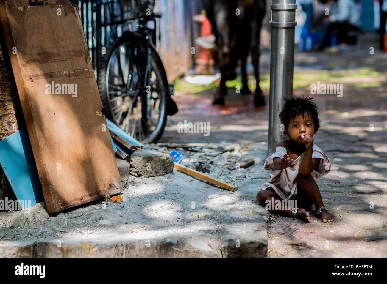 Eine kleine Obdachlosen Straßenkind sitzt am Straßenrand der Kamera mit der Hand heraus suchen. Stockbild