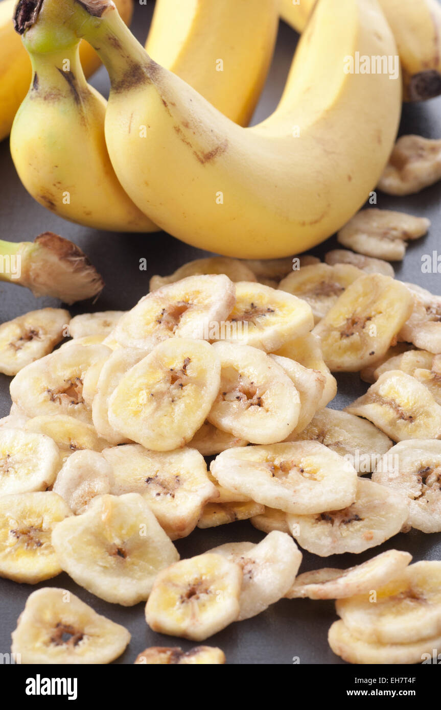 Süßen getrockneten Bananenscheiben mit frischen Bananen im Hintergrund. Stockbild