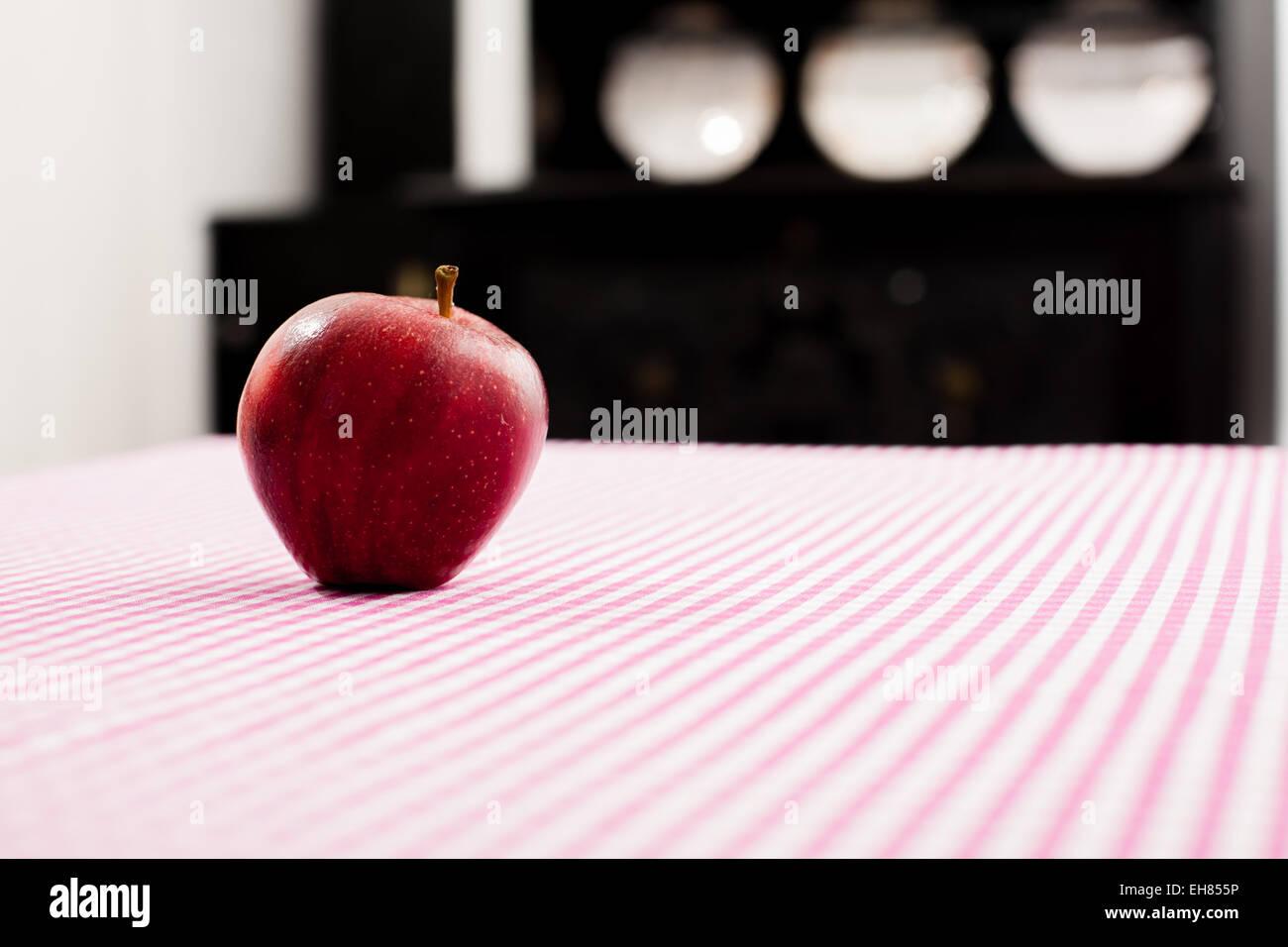 Roter Apfel auf dem aufgegebenen Tischtuch. Stockbild