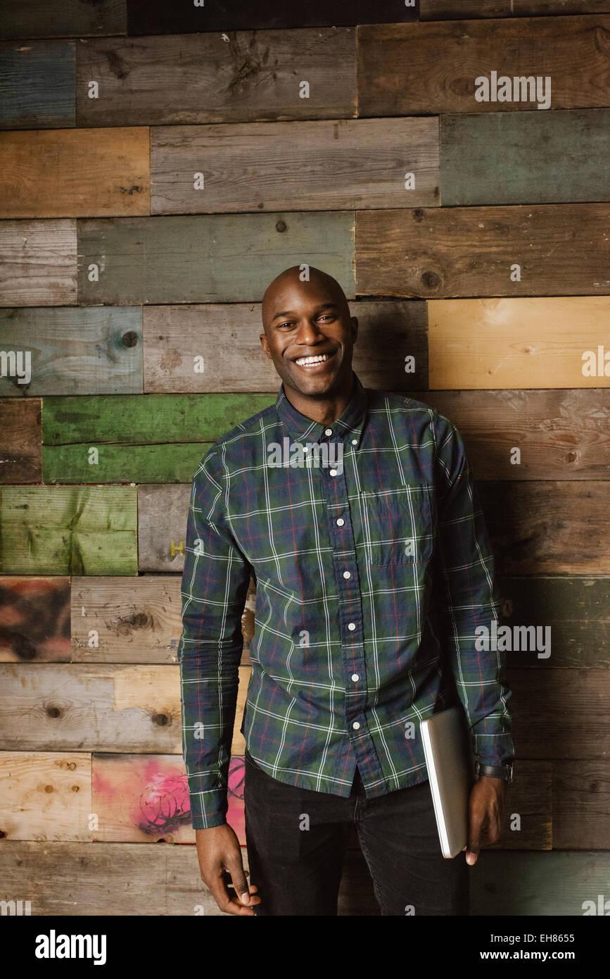 Porträt von glücklich junge Mann, der einen Blick in die Kamera Lächeln, während Sie im Büro Stockbild