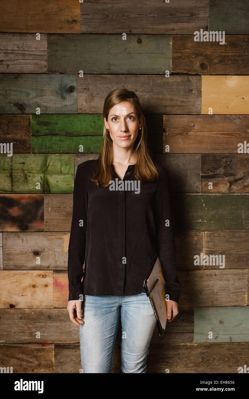 Porträt von schöne junge Geschäftsfrau, stehen gegen eine Holzwand, Blick in die Kamera. Kaukasischen Stockbild