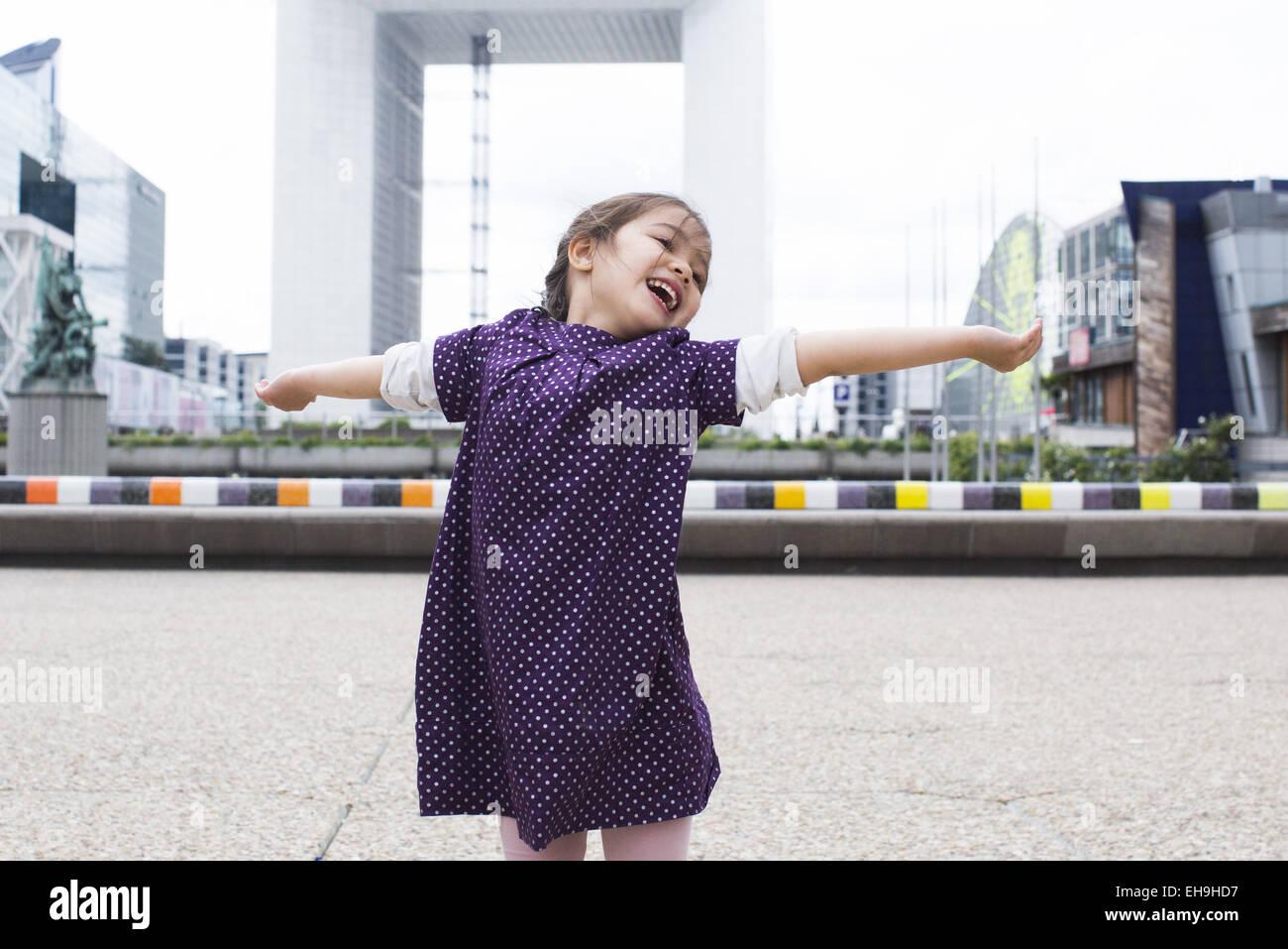 Kleine Mädchen stehen mit ihrem Kopf in den Nacken und die Arme ausgestreckt vor der Grande Arche, Paris, Frankreich Stockbild