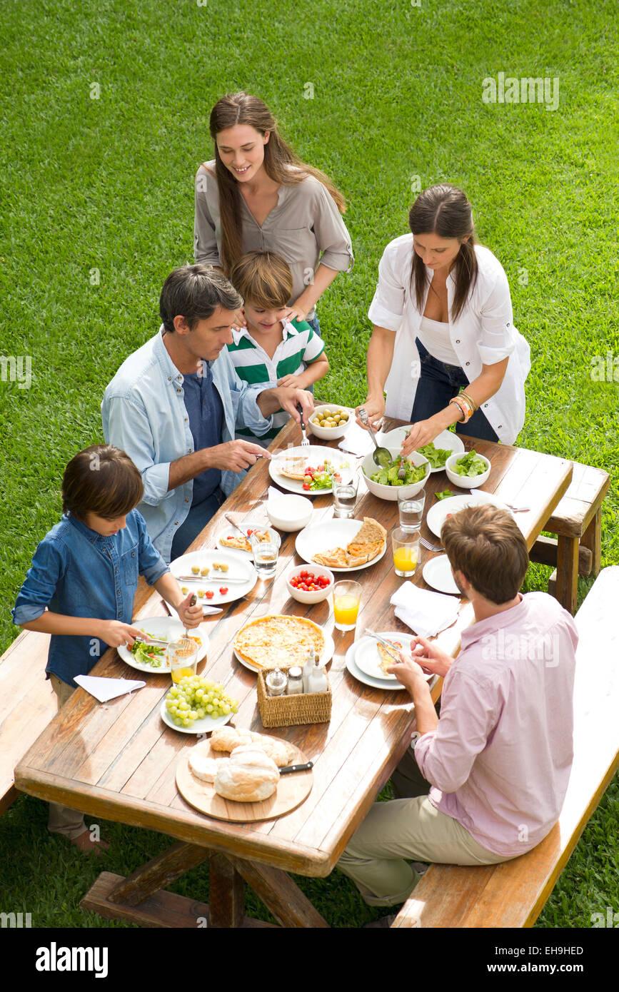 Familie und Freunde genießen gesunde Mahlzeit im freien Stockbild