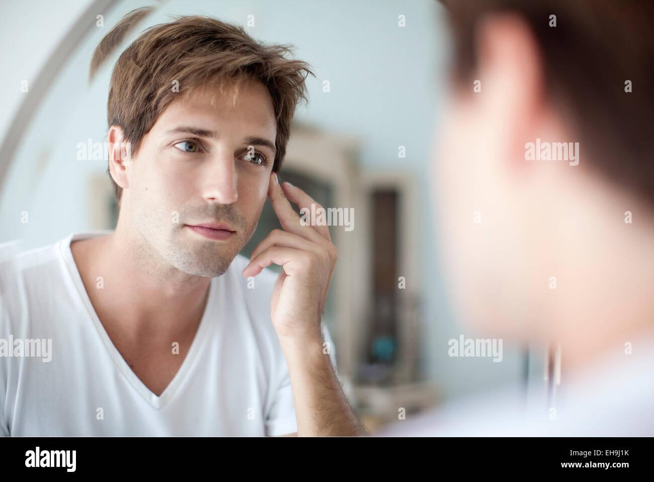 Mann selbst im Spiegel mit Besorgnis über seine Teint betrachten Stockbild