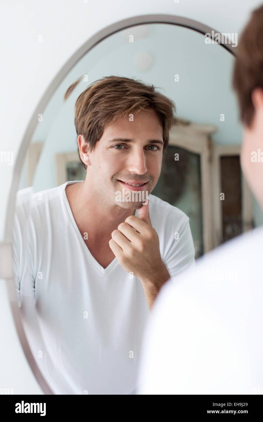 Mann selbst im Spiegel berühren Gesichts Stoppeln zu betrachten Stockbild
