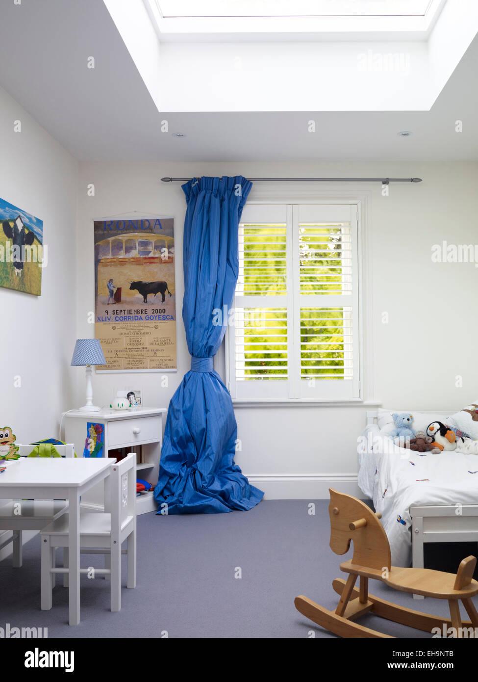Über große blaue Vorhang in Kind Schlafzimmer in Chesilton Road Home, UK Stockfoto