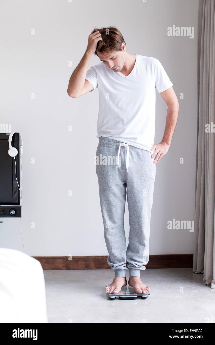 Mann mit einem Gewicht von selbst auf Personenwaage Stockbild