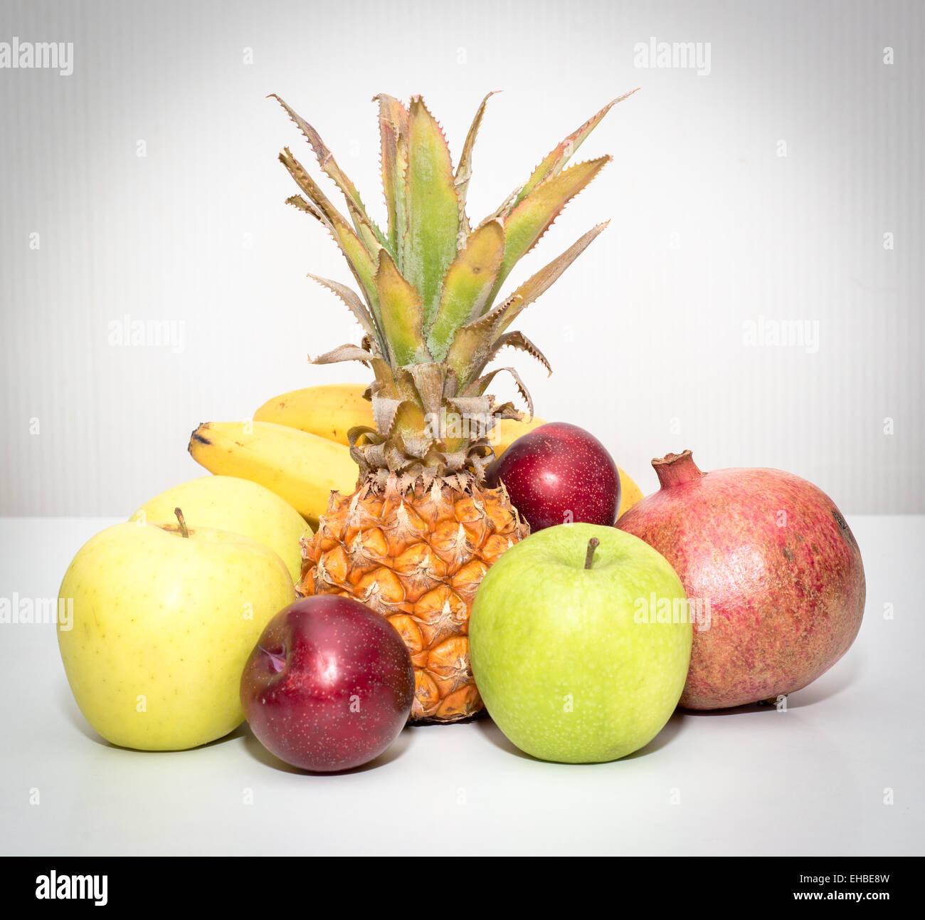 Stillleben mit Früchten Ananas, Äpfel, Bananen, Pflaumen, Granatapfel Stockbild