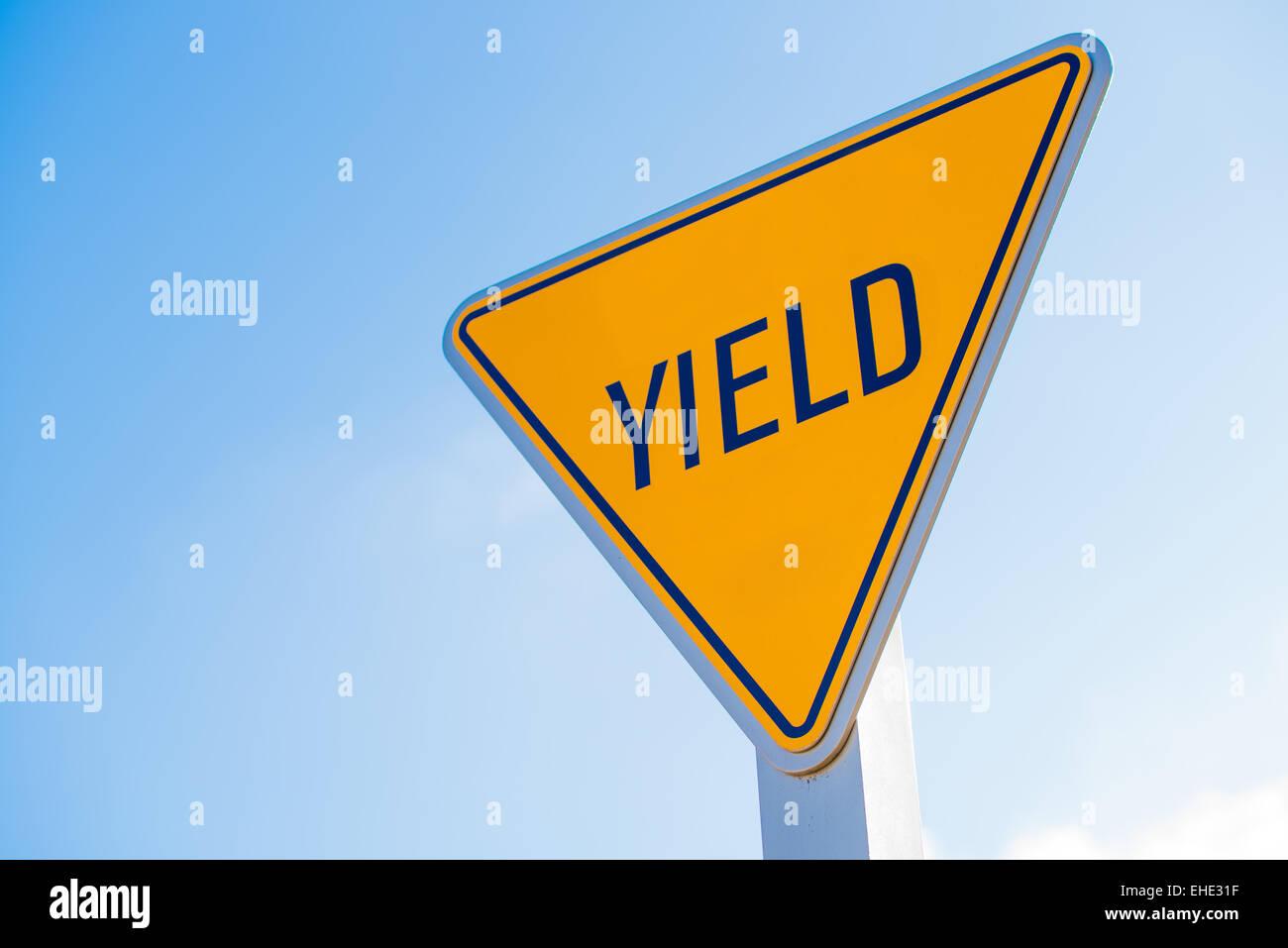 Eine gelbe Ertrag Schild mit einem blauen Himmelshintergrund Stockbild