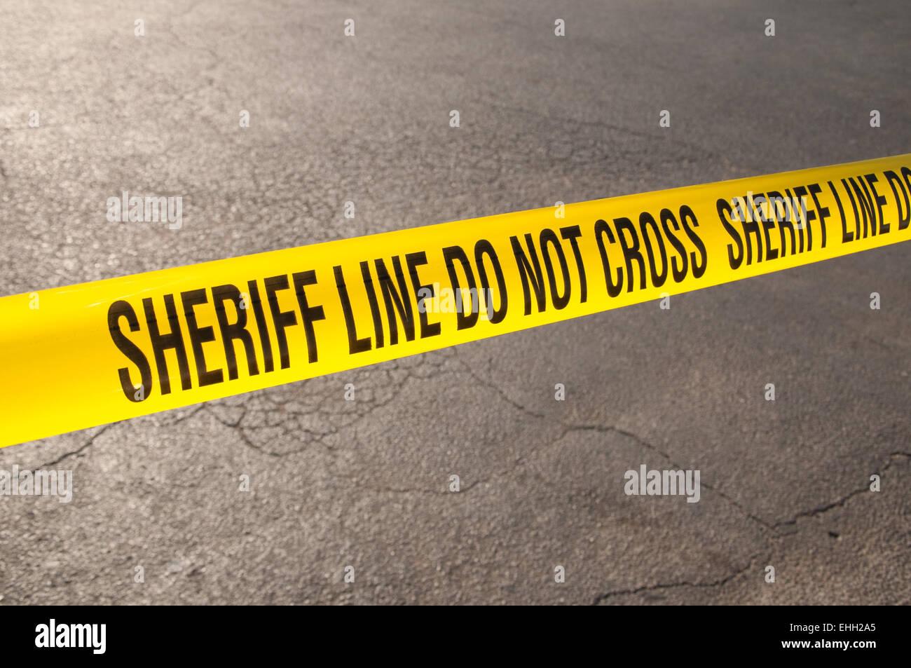 Sheriff-Linie nicht überqueren - Absperrband in urbaner Umgebung Stockbild