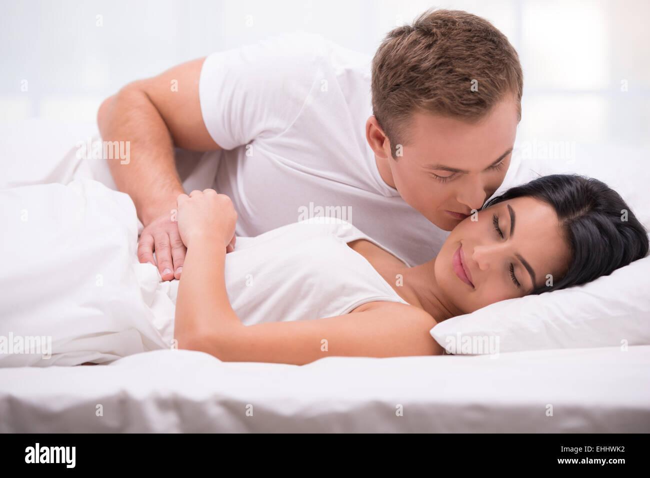 Foto Op Kussen : Junger mann küssen seine schlafende frau stockfoto bild